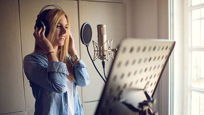 Frau im Ton-Studio singt ins Mikrofon