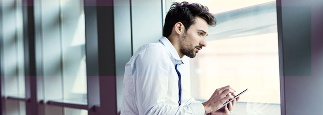 Mann mit Tablet mit Blick aus Fenster
