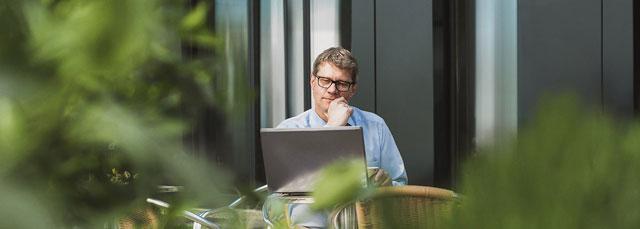 Mann sitzt im Garten und arbeitet am Notebook
