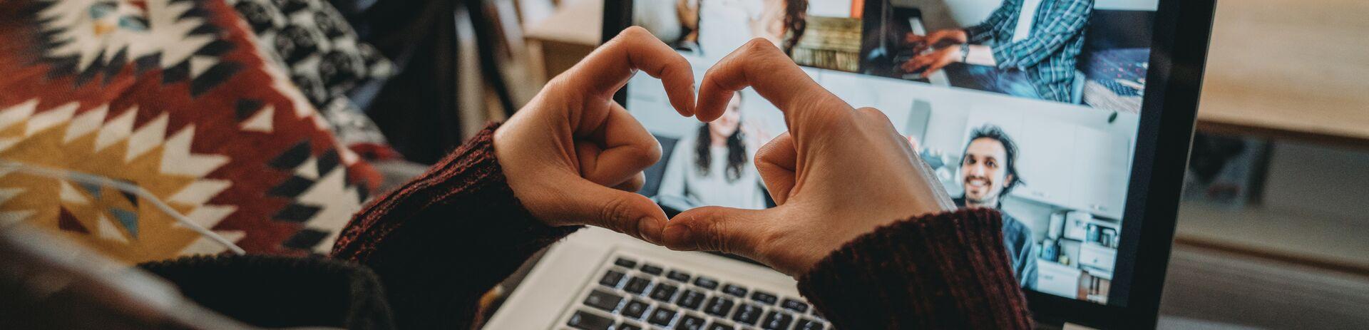 Online-Meeting mit Hand geformtes Herz