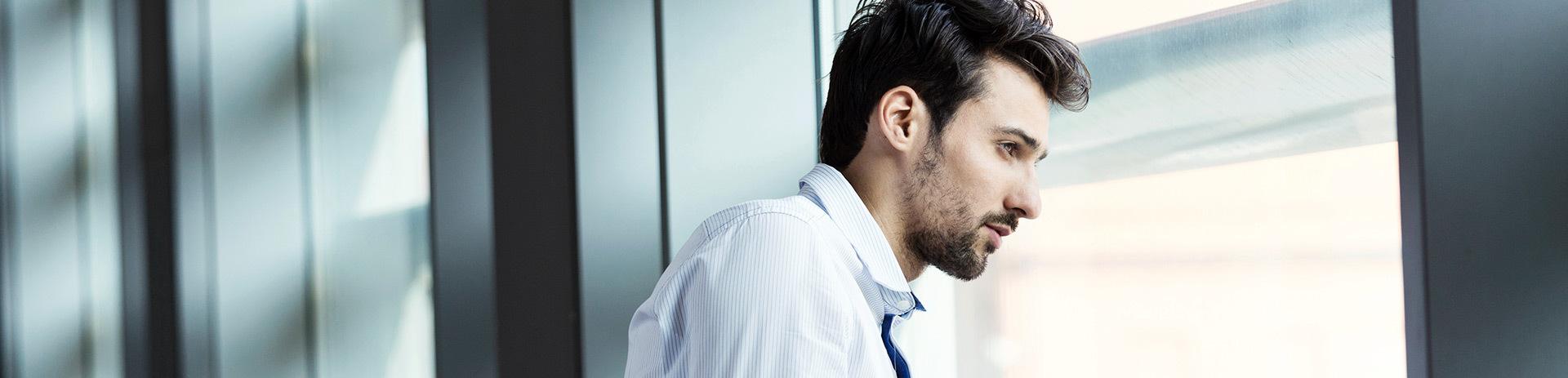 junger Businessman blickt aus Fenster