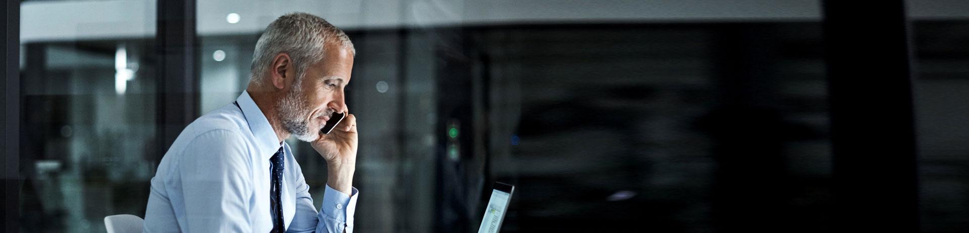 Mann sitzt seitlich vor Bildschirm und telefoniert gleichzeitig mit Smartphone.