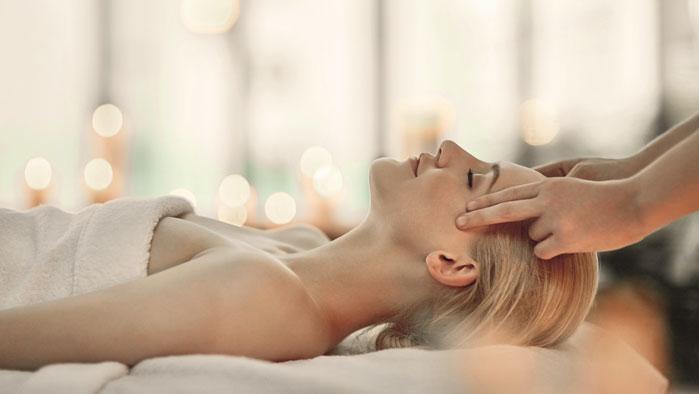 Frau geniesst eine Kopfmassage in Wohlfuehlambiente bei dem A1 Smile Vorteilpartner Themre Wien