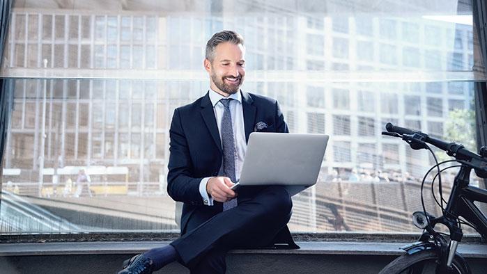 Business-Mann sitzt im Anzug im Freien, neben sich ein Fahrrad, und arbeitet mit einem Notebook