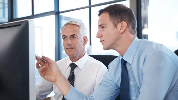 Zwei Männer sitzen vor Bildschirm und reden