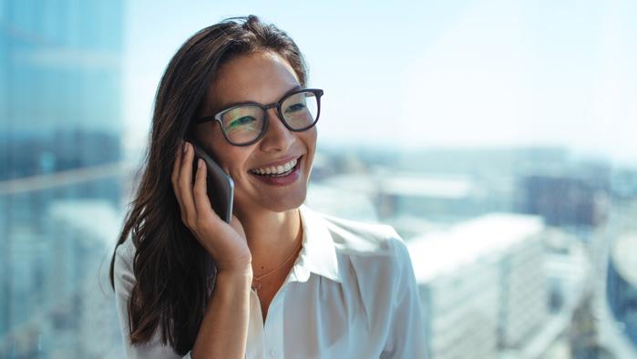 Frau telefoniert mit Smartphone vor Fenster