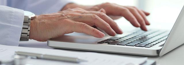 Männerhand tippt auf Notebook-Tastatur