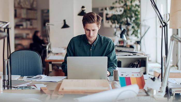 Mann sitzt am Schreibtisch und arbeitet am Laptop
