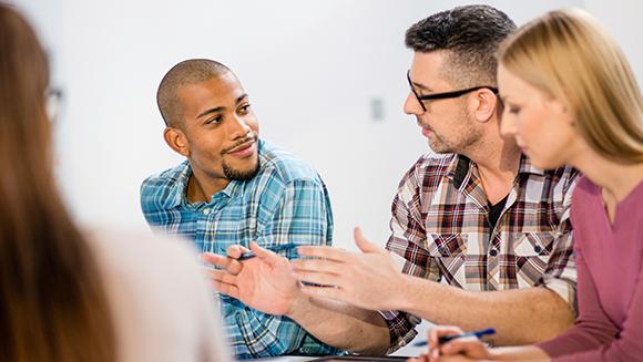 ein paar junge MitarbeiterInnen diskutieren angeregt über ein Thema