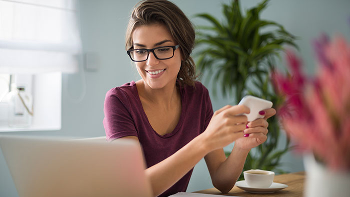 Frau sieht von ihrem Smartphone auf ihren Notebookbildschirm