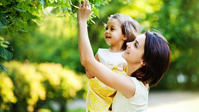 junge Mutter, die mit ihrem Kind einen Strauch in einem Park begutachtet