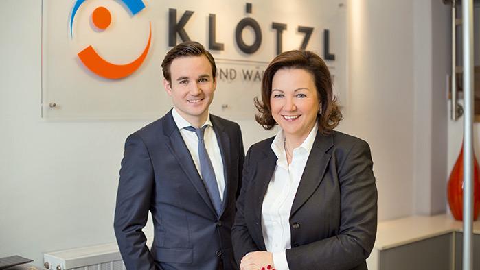 2 Personen im Businessoutfit stehen vor dem Logo der Klötzl Vertriebs GmbH