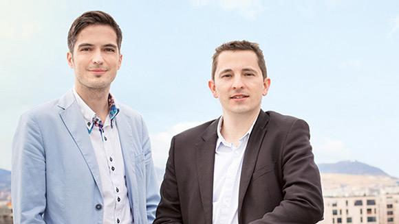 zwei junge Herren im Anzug posieren vor einem Stadtpanorama