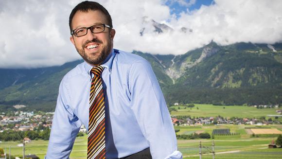 ein Herr in Hemd und Kravatte sitzt; die Hände unten abgestütz; im Hintergrund sieht man eine bergige Landschaft und viel Grün