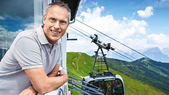 lächelnder Mann im Vordergrund und im Hintergrund sieht man eine Gondel der Schmittenhöhebahn im Sommer