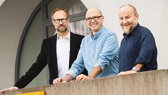 Drei Männer stehen hinter einer hüfthohen Mauer vor dem Gebäude der Lebenshilfe Vorarlberg