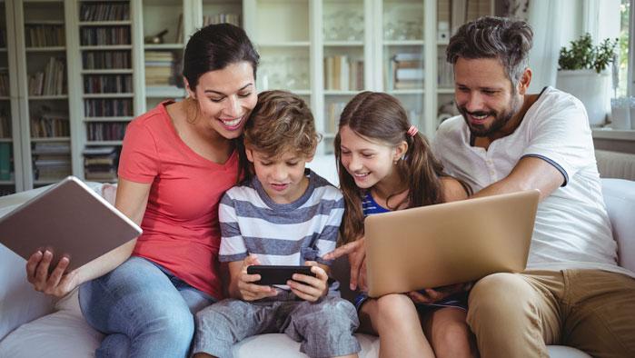 Familie, die auf einer Couch sitzt und auf mehreren Geräten gleichzeitig im Internet surft