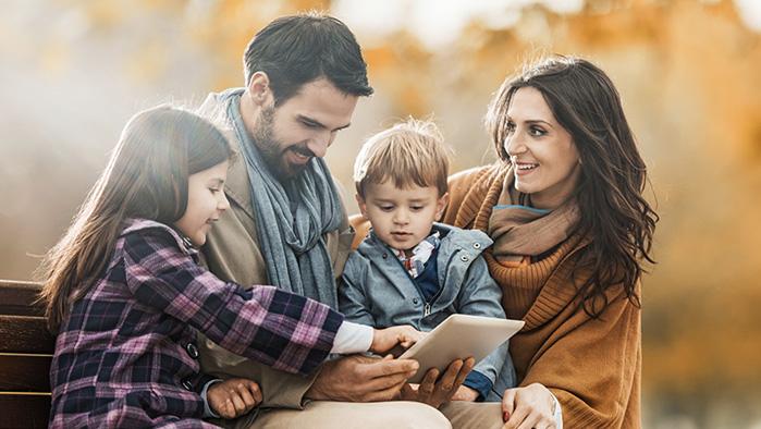 eine junge Familie mit zwei Kindern sitzt auf einer Parkbank und sieht auf ein Tablet