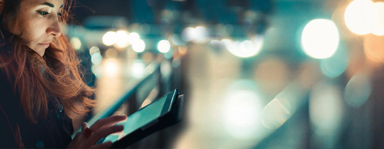 Frau steht auf Brücke und sieht in ein Tablet