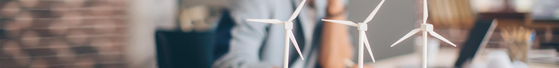 drei kleine Windräder aus Plastik, die als Dekoration auf einem Schreibtisch stehen
