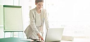 Frau, die in einem Meeting-Raum am Laptop arbeitet