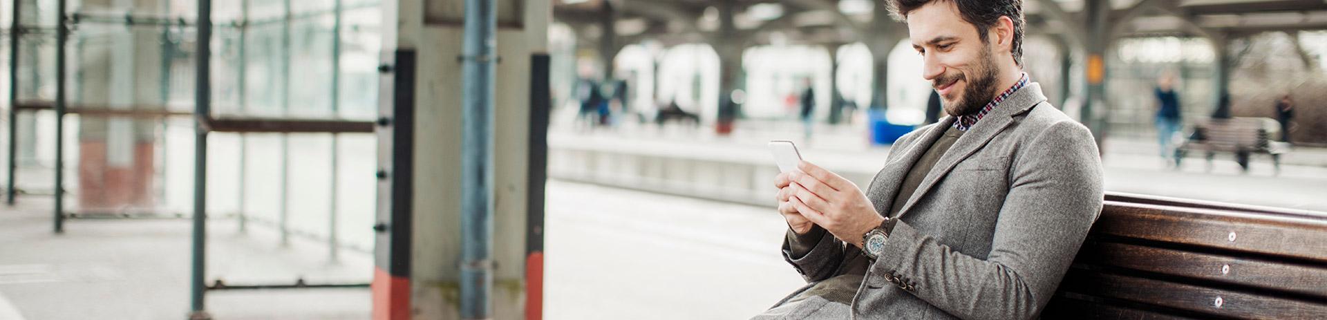 Mann sitzt am Bahnhof auf einer Bank und benutzt ein Smartphone