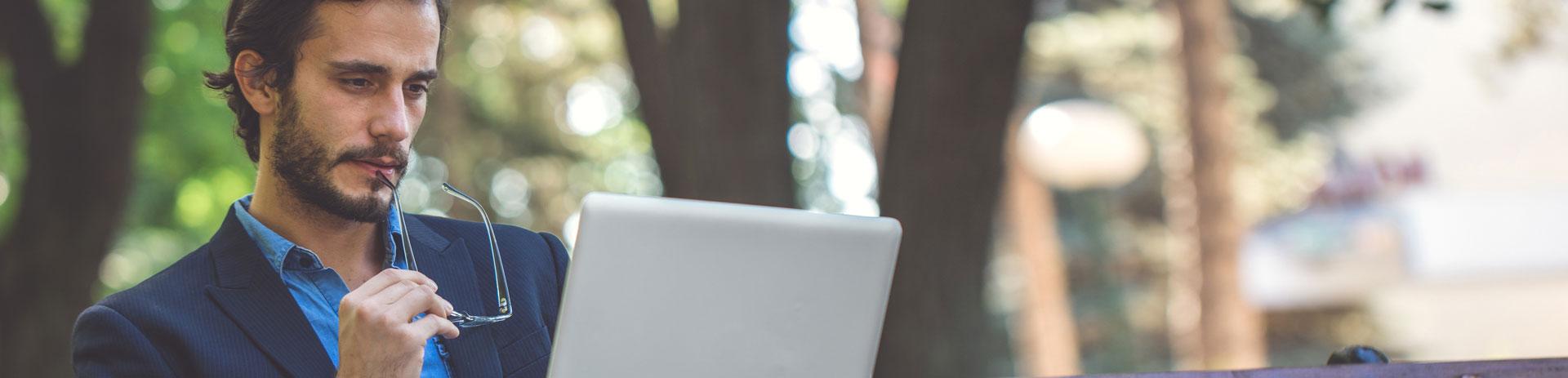 Mann sitzt auf Parkbank mit Notebook