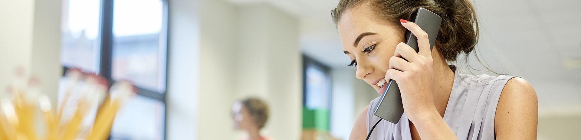 Frau hält Festnetz-Hörer zum Ohr