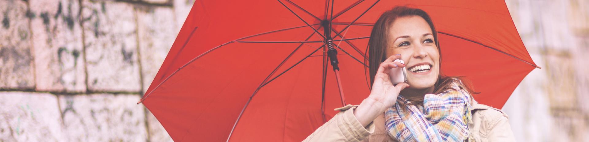 Frau unter einem roten Regenschirm, die telefoniert