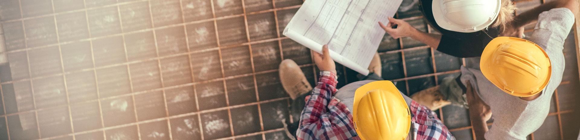 Drei Maenner planen gemeinsam ein Projekt, das Bild symbolisiert die Unterstuetzung von Bauprojekten und Bauunternehmen durch A1 Software-, Internet- und Kommunikationsloesungen.