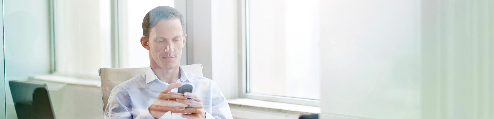 Geschäftsmann, der einen Blick auf sein Handy wirft