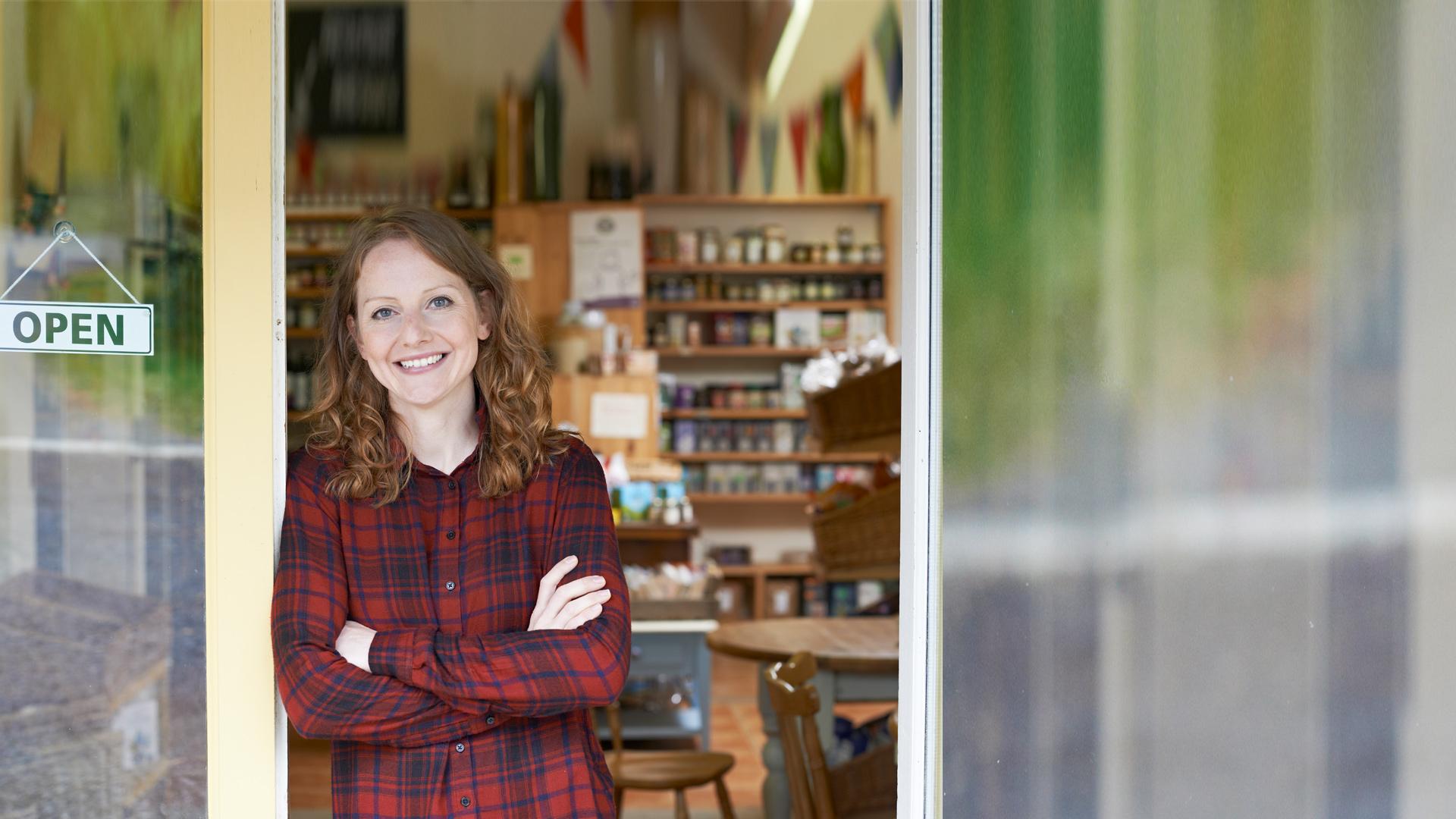 Junge Frau steht in Tür von Geschäftslokal