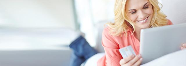 Frau liegt mit Tablet auf dem Sofa mit der Kreditkarte in der Hand