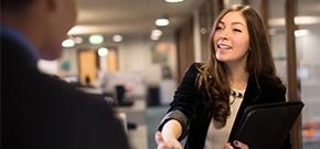 eine junge, braunhaarige Frau reicht dem Personalverantwortlichen die Hand