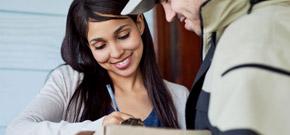 Frau uebernimmt gluecklich mit Unterschrift ein Paket und symbolisiert die Zufriedenheit der Kunden durch die Effizienzsteigerung von Dienstleistungsunternehmen mittels A1 Software-, Internet- und Telco-Produkten.