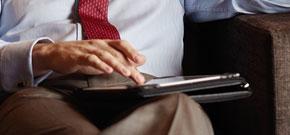 Mann sitzt mit Tablet auf dem Schoß in der Hotellobby und symbolisiert die Wichtigkeit der software- und telekommunikationsbasierenden Services für die Hotel- und Gastronomiebranche.