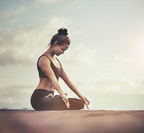 eine Dame sitzt am Strand und macht eine Yogaübung