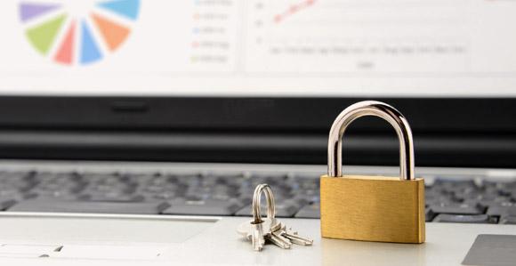 Laptop mit Schloss und Schlüssel vor Tastatur
