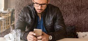Businessmal in Lederjacke und Smartphone in der Hand