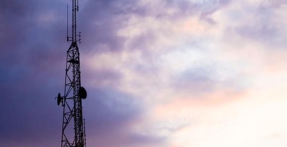 Man sieht den Masten einer Mobilfunkanlage, der in den violett und blau gefärbten Himmel ragt