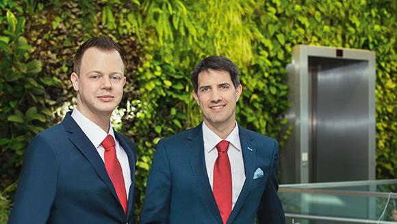 2 Männer im blauen Anzug und roter Krawatte stehen vor einer verwachsenen Hauswand; im Hintergrund sieht man einen Aufzug