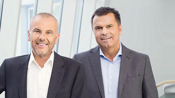 zwei Herren im Anzug stehen vor einer Fensterfront