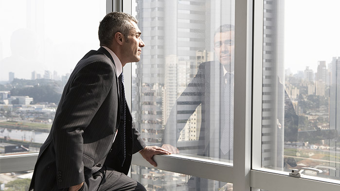 Geschäftsmann, der an einer Fensterfront steht (Getty Images)