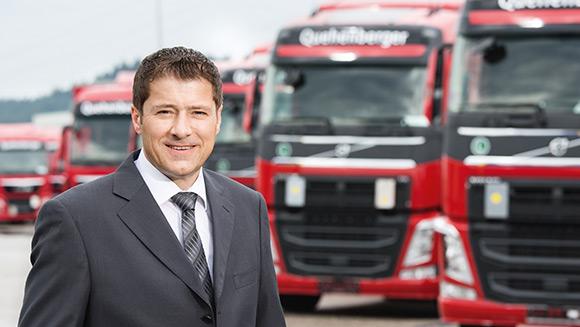 ein Mann im Anzug steht vor einer Reihe von LKWs, die in rot gehalten sind