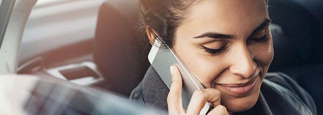 Frau sitzt auf der Rückbank eines Wagens und telefoniert mit Smartphone