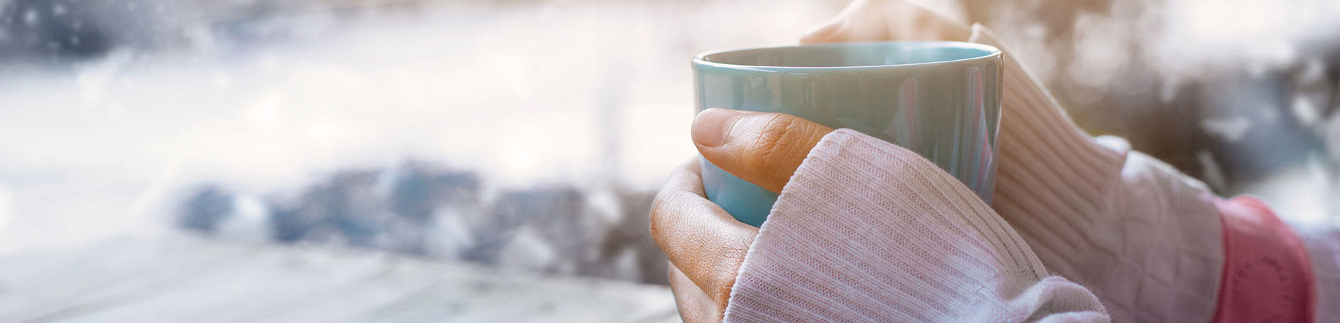 Hände, die eine Tasse Tee halten
