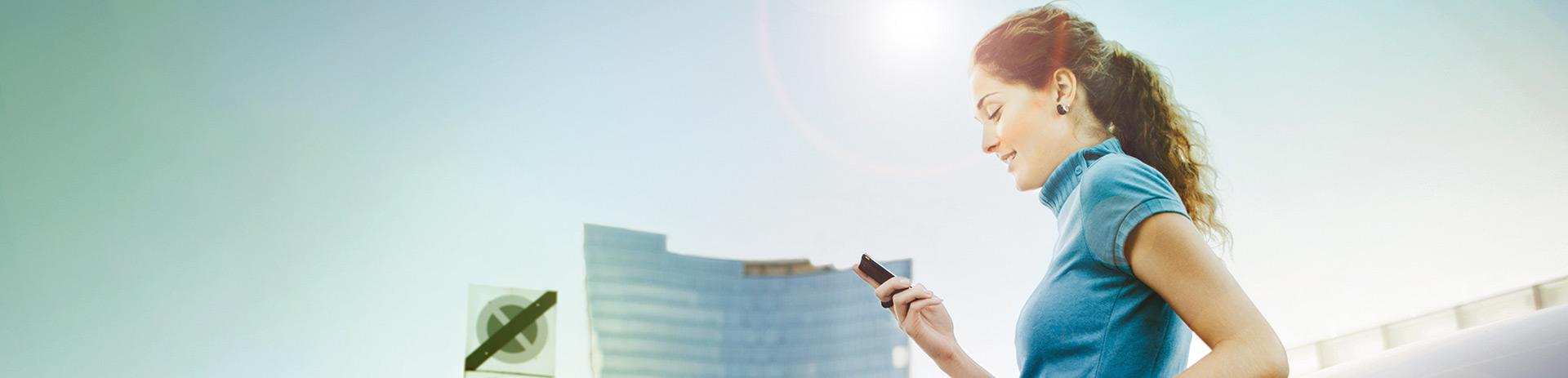eine junge Dame steht vor einem großen Bürokomplex und sieht auf ihr Smartphone