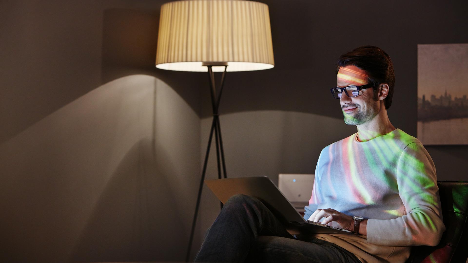 Junger Mann mit Laptop genießt schnellere Internetgeschwindigkeiten