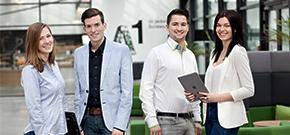 zwei männliche und 2 weibliche Graduates stehen mit Laptop und Tablet in der Hand in der Empfangshalle von A1