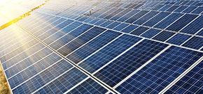 Reihen mit Solarzellen; im Hintergrund sieht man Sonnenstrahlen